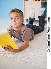 Little boy sitting on floor reading