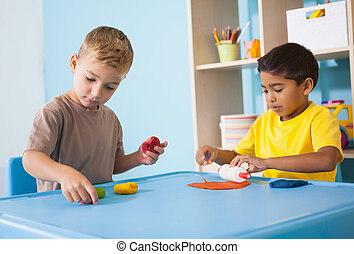 Cute little boys playing with modelling clay in classroom at...