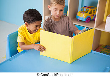 Cute little boys reading at desk in classroom at the nursery...