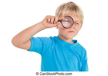 Cute little boy looking through magnifying glass on white...