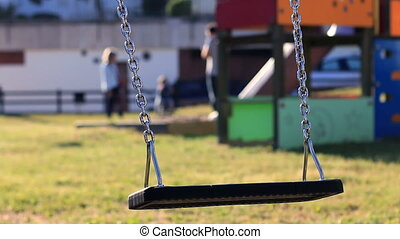 Empty Swing Swinging 01 - An empty swing swinging in the...