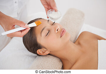 Beautiful brunette getting a facial at the health spa
