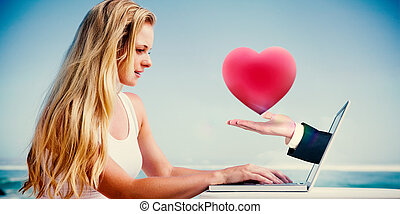 Composite image of pretty blonde using her laptop at the...