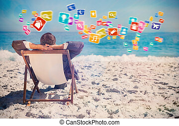 Composite image of young businessman relaxing on his sun lounger