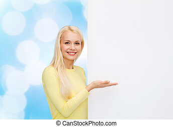 smiling woman in sweater with blank white board - people,...