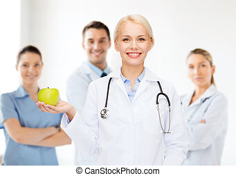 smiling female doctor with green apple - healthcare and...