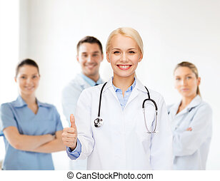 smiling female doctor showing thumbs up - healthcare and...