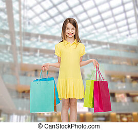 smiling little girl in dress with shopping bags - shopping,...