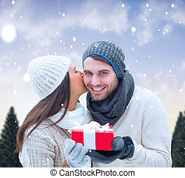 Composite image of winter couple holding gift - Winter...