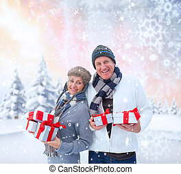 Composite image of festive mature couple holding christmas gifts