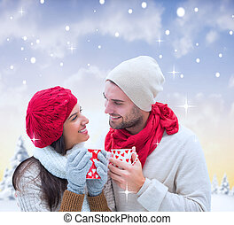 Composite image of winter couple holding mugs - Winter...