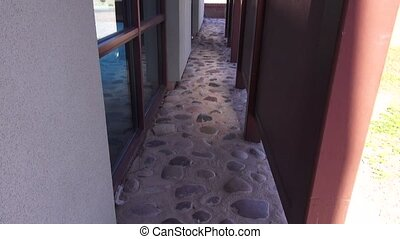Stone Walkway by Window - A stone walkway between a sunshade...