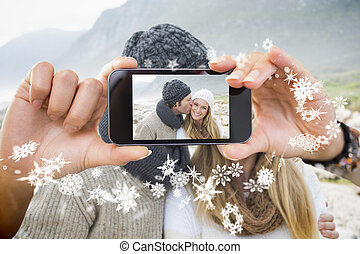 Composite image of hand holding smartphone - Hand holding...