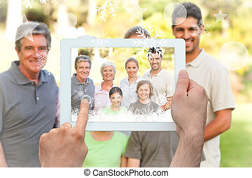 Hands holding tablet pc against family in the park
