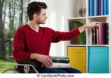 Man on wheelchair placing books on shelf