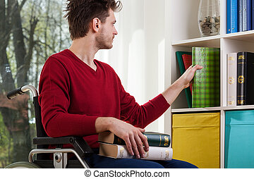 Disabled man cleanig up a bookshelf - Young disabled man...
