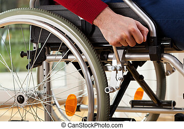Wheelchair breaks - Close-up of disabled man using...