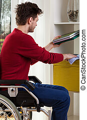 Man on wheelchair dusting shelves - Youmg man on wheelchair...