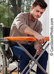 Man on wheelchair preparing iron board - Young man on...