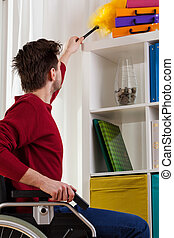 Disabled man doing dusting - Disabled man doing shelf...