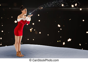 Composite image of pretty santa girl blowing over her hands...