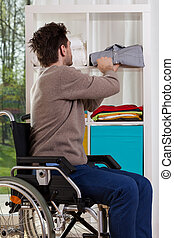 Disabled man placing shirt on shelf - Young disabled man...