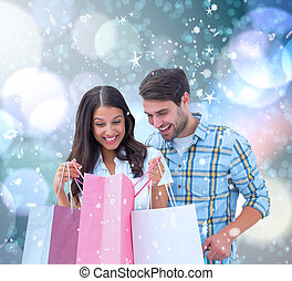 Composite image of happy couple with shopping bags - Happy...