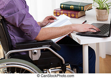 Disabled man studying at home - Young disabled man studying...
