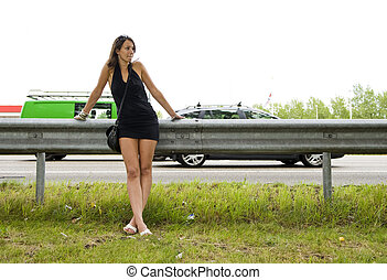 highway woman - Young woman in a black mini dress leaning on...