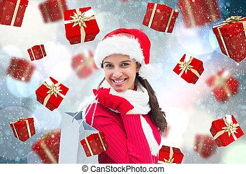 Composite image of festive brunette holding shopping bag