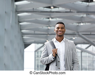 African american man smiling with bag at airport - Close up...