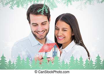 Composite image of attractive young couple holding a model house