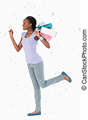 Composite image of woman with credit card and shopping on...