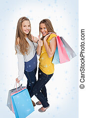 Composite image of two beautiful young women with shopping...