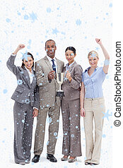 Composite image of happy business team holding a cup - Happy...