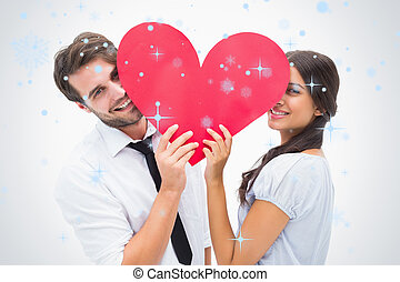 Composite image of couple smiling at camera holding a heart...