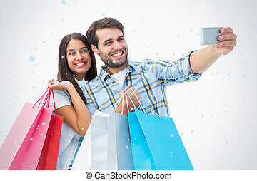 Composite image of attractive young couple with shopping...