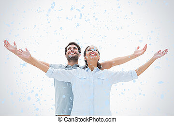 Composite image of cute couple standing with arms out - Cute...