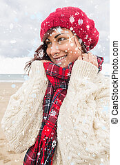 Composite image of cute smiling woman in warm clothing...