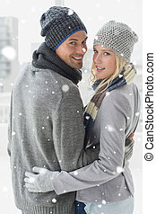 Composite image of cute couple in warm clothing hugging...