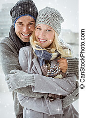 Composite image of cute couple in warm clothing smiling at...