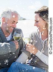 Composite image of couple enjoying white wine on picnic at...