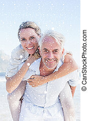 Composite image of man giving his smiling wife a piggy back...
