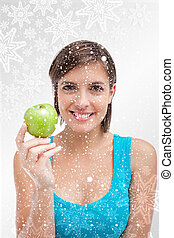 Composite image of young woman holding a green apple in her righ