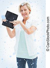 Composite image of happy mature woman pointing to tablet pc...