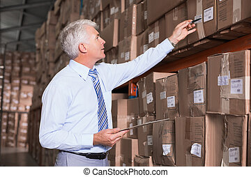 Warehouse manager checking his inventory in a large...
