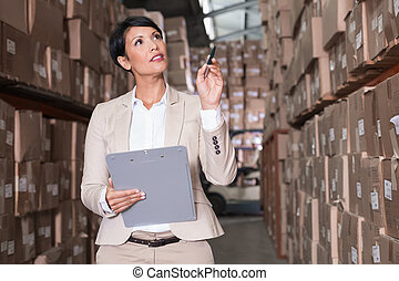 Warehouse manager checking her inventory in a large...