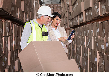Warehouse worker moving boxes on trolley talking to manager...