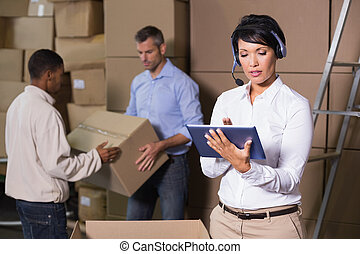 Pretty warehouse manager using tablet during busy period in...