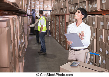 Pretty warehouse manager checking inventory in a large...